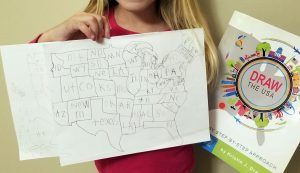 Little girl holding her drawn map of the USA and the book Draw the USA