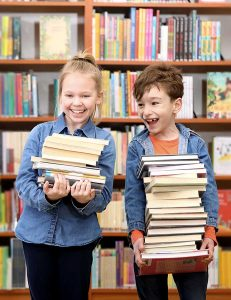 Girl and Boy laughing holding a stack of books