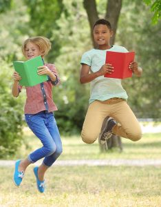 Girl and Boy with books jumping for joy
