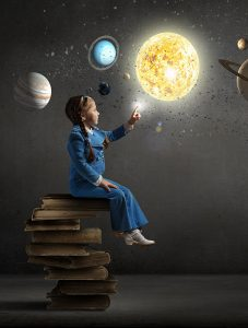 Little girl sitting on a stack of books touching the sun
