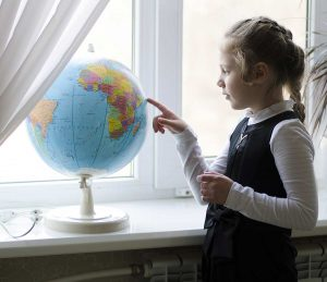 girl playing with a globe, looking for a country, at home school