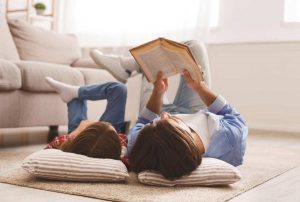 Little daughter and daddy enjoying time together, laying on floor at home, man reading book to his cute daughter