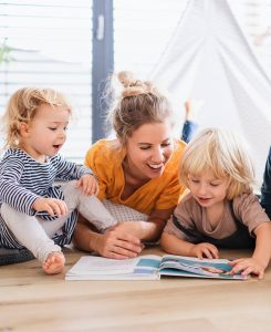 Mom with two small children indoors in bedroom reading a book.